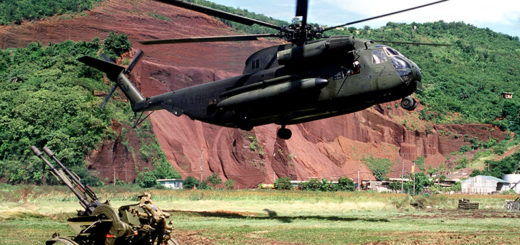 A CH-53 Sea Stallion helicopter hovers above the ground near a Soviet ZU-23 anti-aircraft weapon prior to picking it up during Operation URGENT FURY.
