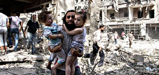 A Syrian man carries his two two girls a...A Syrian man carries
