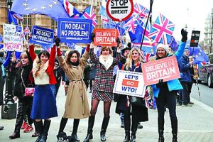 Leavers hold up signs next to pro-European demonstrators protesting opposite the Houses of Parliament in London, Tuesday, Jan. 15, 2019. Britain's Prime Minister Theresa May is struggling to win support for her Brexit deal in Parliament. Lawmakers are due to vote on the agreement Tuesday, and all signs suggest they will reject it, adding uncertainty to Brexit less than three months before Britain is due to leave the EU on March 29. (AP Photo/Frank Augstein)