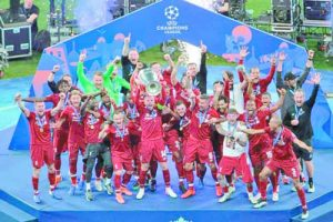 Liverpool's Jordan Henderson lifts the trophy after winning the Champions League final soccer match between Tottenham Hotspur and Liverpool at the Wanda Metropolitano Stadium in Madrid, Saturday, June 1, 2019. (AP Photo/Emilio Morenatti)