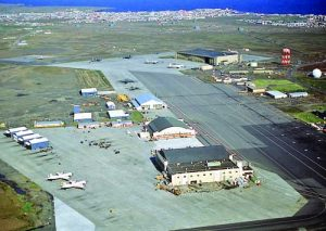 An aerial view of the ramp areas and facilities of the 57th Fighter Interceptor Squadron, with other facilities in the background.
