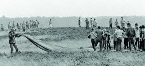 A crowd gathers in a field to watch a paratrooper fold his parachute just after he was airdropped from a U.S. Air Force C-130 during exercise Reforger/Autumn Forge 1980.  Autumn Forge is a reserve airdrop taking place here and in Germany and involving mostly U.S. and British troops and equipment.