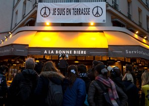 """TOPSHOT - A banner reading """"Je suis en terrasse"""" hangs above as journalists gather in front of the bar """"A la Bonne Biere"""" in Paris on December 4, 2015, during its reopening after it was hit during a series of coordinated attacks in and around Paris on November 13. The Paris bar where five people were killed by jihadist gunmen in the November 13 attacks is the first of the attacked bars to re-open, in an emotional step in the city's struggle to regain normality. / AFP / KENZO TRIBOUILLARD"""