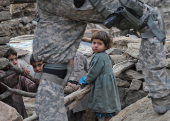 Afghan children look on as a US soldier from the Provincial Reconstruction team (PRT) Steel Warriors patrols in the mountains of Nuristan Province on December 19, 2009. US President Barack Obama has pledged an extra 30,000 troops to bolster an international force of 113,000 already fighting a Taliban-led insurgency that has become more virulent and deadly over the past year. AFP Photo/Tauseef MUSTAFA (Photo credit should read TAUSEEF MUSTAFA/AFP via Getty Images)