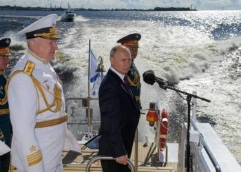 """ST PETERSBURG, RUSSIA - JULY 26, 2020: Russia's President Vladimir Putin (C), Admiral Nikolai Yevmenov (L front), Commander-in-Chief of the Russian Navy, and Russia's Defense Minister Sergei Shoigu (R background) inspect warships in the Kronstadt roadstead aboard the Raptor boat ahead of a military parade on Russian Navy Day. Alexei Druzhinin/Russian Presidential Press and Information Office/TASS  Ðîññèÿ. Ñàíêò-Ïåòåðáóðã. Ïðåçèäåíò ÐÔ Âëàäèìèð Ïóòèí (â öåíòðå), ãëàâíîêîìàíäóþùèé Âîåííî-Ìîðñêèì Ôëîòîì Ðîññèè, àäìèðàë Íèêîëàé Åâìåíîâ (ñëåâà íà ïåðâîì ïëàíå) è ìèíèñòð îáîðîíû ÐÔ Ñåðãåé Øîéãó (ñïðàâà íà âòîðîì ïëàíå) íà áîðòó êàòåðà """"Ðàïòîð"""" âî âðåìÿ îáõîäà ïàðàäíîé ëèíèè áîåâûõ êîðàáëåé íà Êðîíøòàäòñêîì ðåéäå ïåðåä íà÷àëîì Ãëàâíîãî âîåííî-ìîðñêîãî ïàðàäà â ÷åñòü Äíÿ Âîåííî-Ìîðñêîãî Ôëîòà Ðîññèè. Àëåêñåé Äðóæèíèí/ïðåññ-ñëóæáà ïðåçèäåíòà ÐÔ/ÒÀÑÑ"""