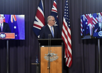 Australia's Prime Minister Scott Morrison, center, appears on stage with video links to Britain's Prime Minister Boris Johnson, left, and U.S. President Joe Biden at a joint press conference at Parliament House in Canberra, Thursday, Sept. 16, 2021. The leaders are announcing a security alliance that will allow for greater sharing of defense capabilities — including helping equip Australia with nuclear-powered submarines. (Mick Tsikas/AAP Image via AP)