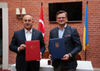 """This handout picture taken and released by Ukrainian Foreign Affairs press-service on October 7, 2021 shows Ukrainian Foreign minister Dmytro Kuleba (R) and his Turkish counterpart Mevlut Cavusoglu holding folders with signed documents during their talks in Lviv. (Photo by STR / Ukrainian Foreign Affairs press-service / AFP) / RESTRICTED TO EDITORIAL USE - MANDATORY CREDIT """"AFP PHOTO /Ukrainian Foreign Affairs press-service """" - NO MARKETING - NO ADVERTISING CAMPAIGNS - DISTRIBUTED AS A SERVICE TO CLIENTS"""